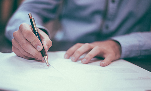 A person signs paperwork